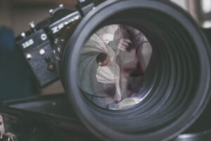 Woman posing in lingerie reflected in the camera lens