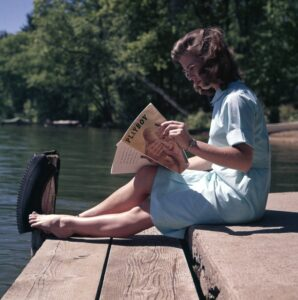 woman reading a playboy adult magazine