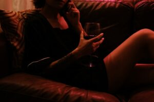 attractive lady lying on the couch with a glass of wine