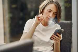 person vaping from an electronic cigarette while on their cellphone