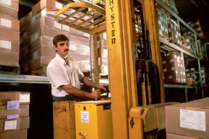 man using forklift to store products in a warehouse